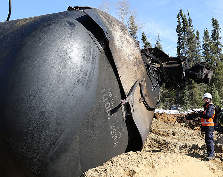 Image of a TSB investigator standing beside a damaged tank car
